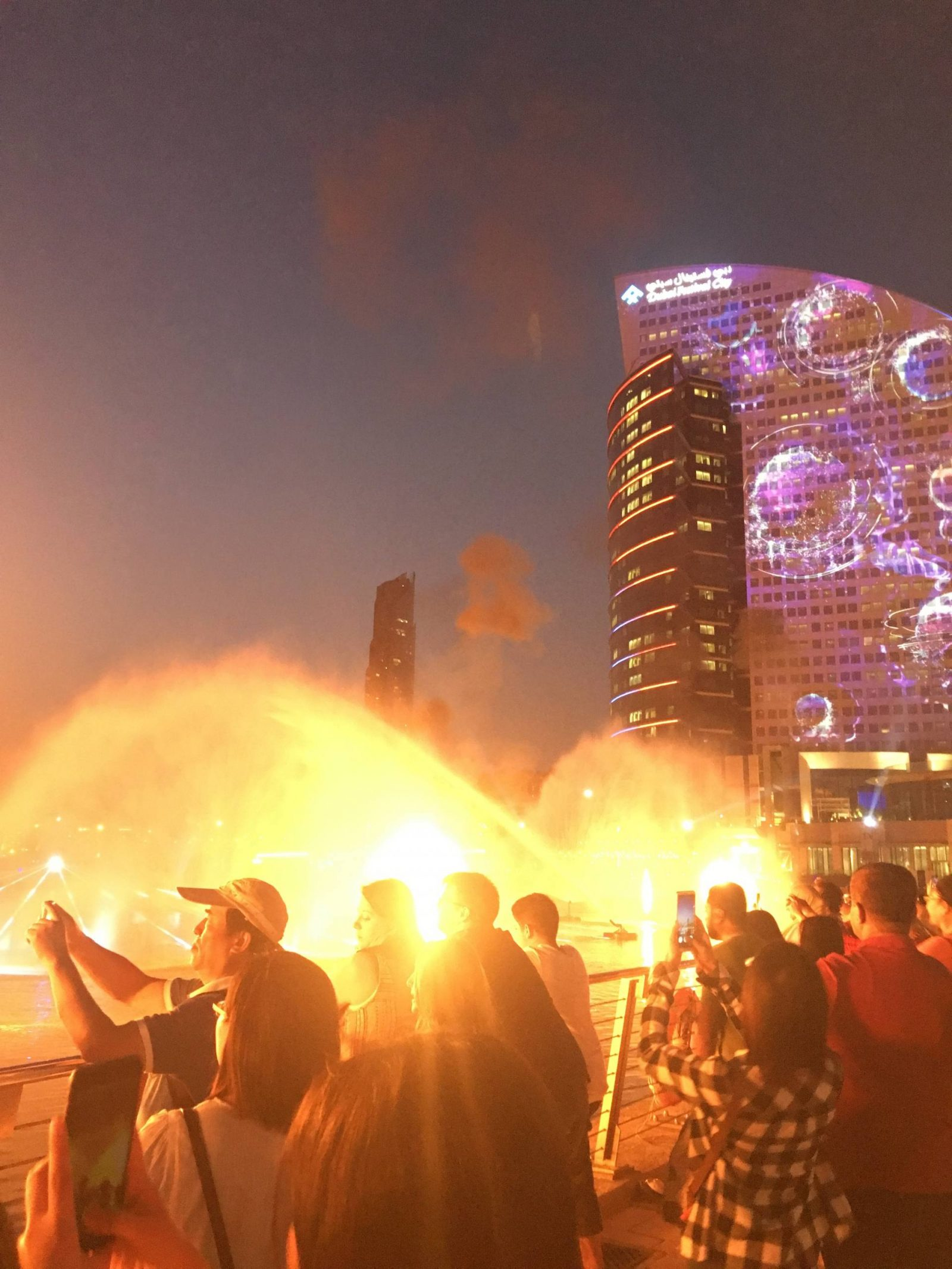 A crowd watches flaming fireworks and a light projection onto a building at IMAGINE, Dubai Festival City Mall
