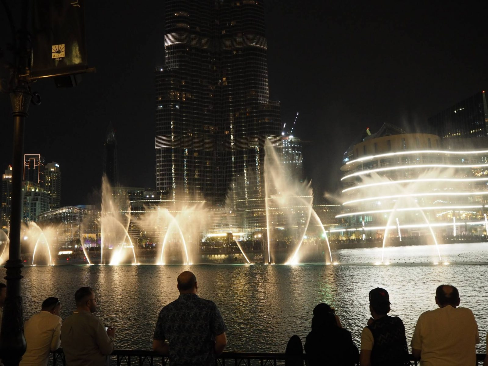 Silhouetted people watch the Dubai Fountain show by night