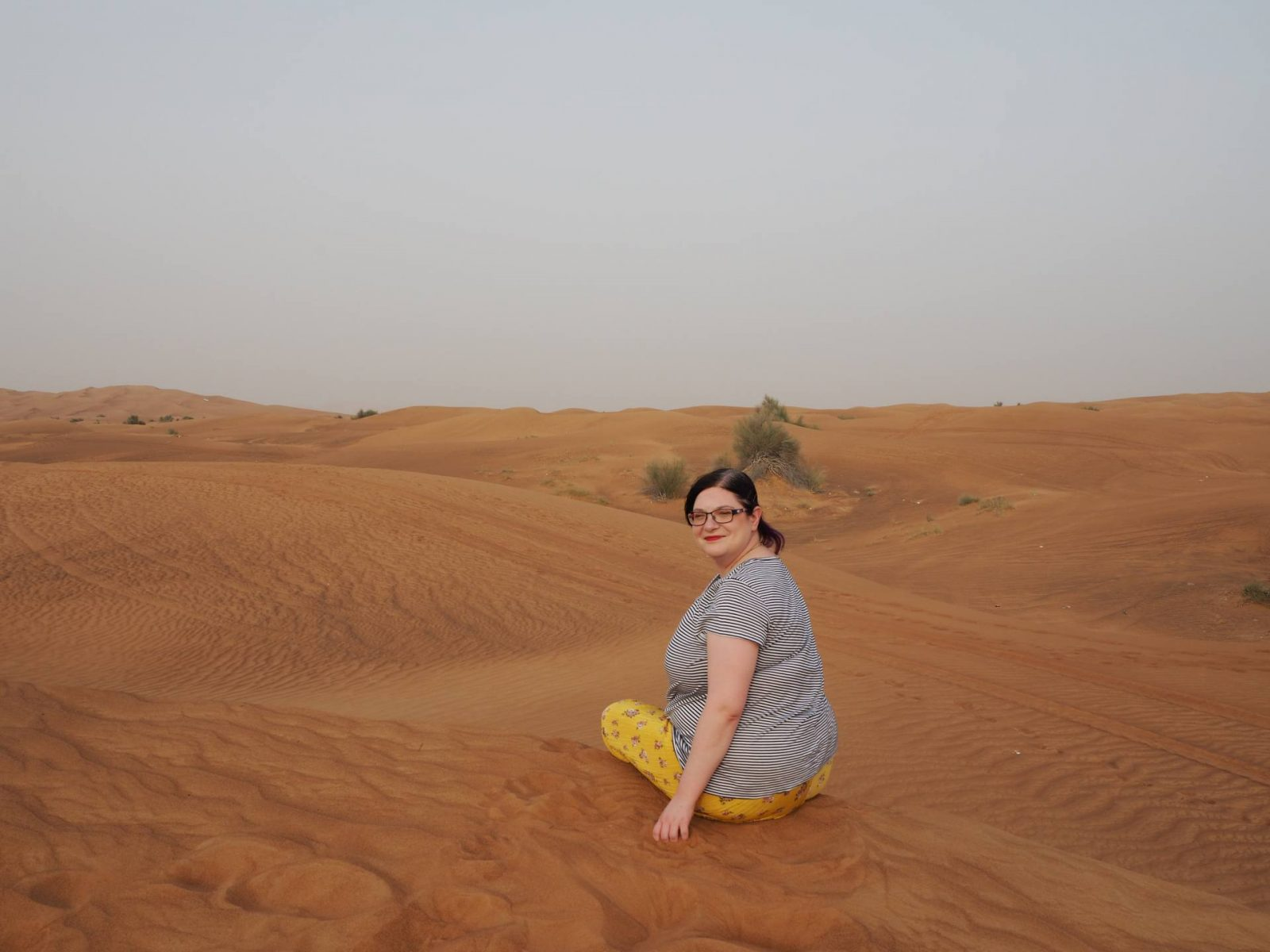 Last Year's Girl sitting on top of a sand dune as the desert stretches out in front of her