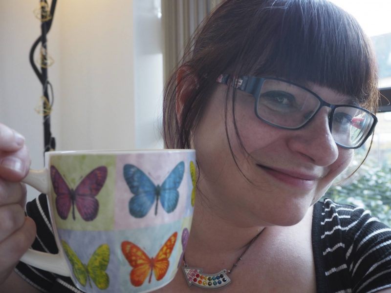 Dark-haired girl with large butterfly-print coffee mug