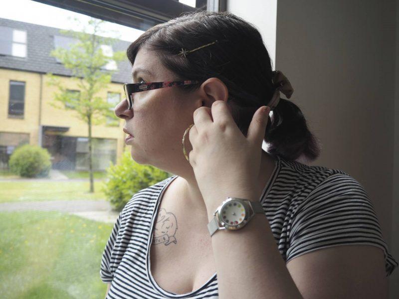 Last Year's Girl looking out of window wearing Mr Jones Cyclops rainbow dial watch