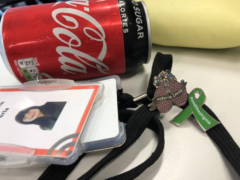Why I talk about my mental health at work: work lanyard with mental health awareness green ribbon