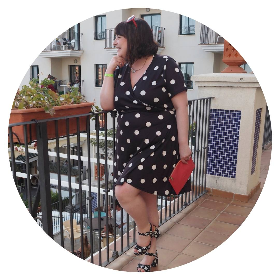 Last Year's Girl stands on a balcony in Benalmadena, wearing a Pink Clove polka-dot dress.
